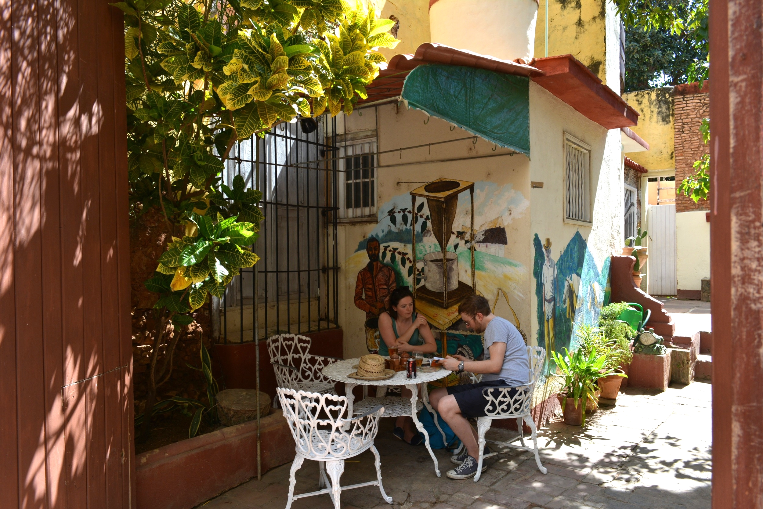 Travelers below a painting of a cafetera.