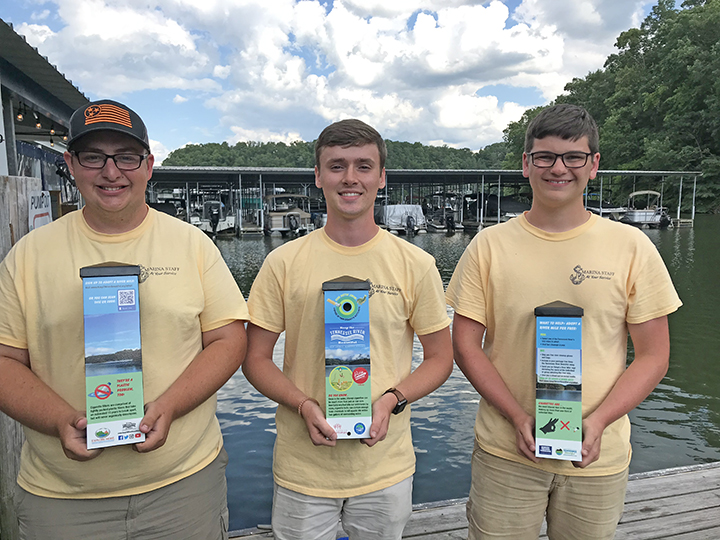 Staff at Caney Creek Marina show off their site's new cigarette waste receptacles.