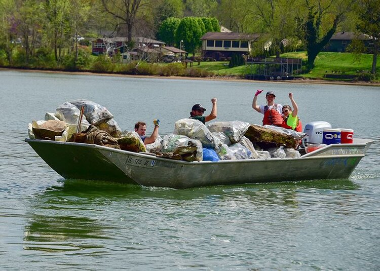 KTNRB volunteers ride back into shore on a Living Lands & Waters boat at an April 2019 cleanup in Oak Ridge, TN.
