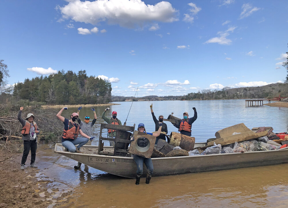 Volunteers celebrate filling up a boat on Fort Loudoun Lake of the Tennessee River during the Knoxville/Louisville, TN cleanup.