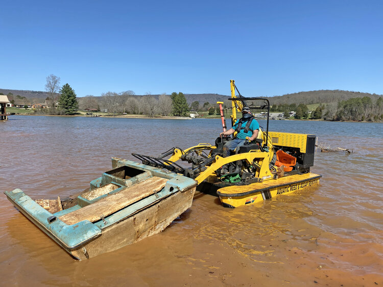 Tennessee Aquatic Weed Removal, a new, local business, removes a piece of an abandoned boat.