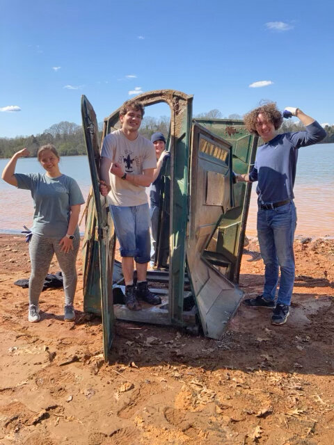 Volunteers pulled a full port-a-john that was partially buried in shallow water at the Knoxville/ Louisville, TN Cleanup on Sunday.