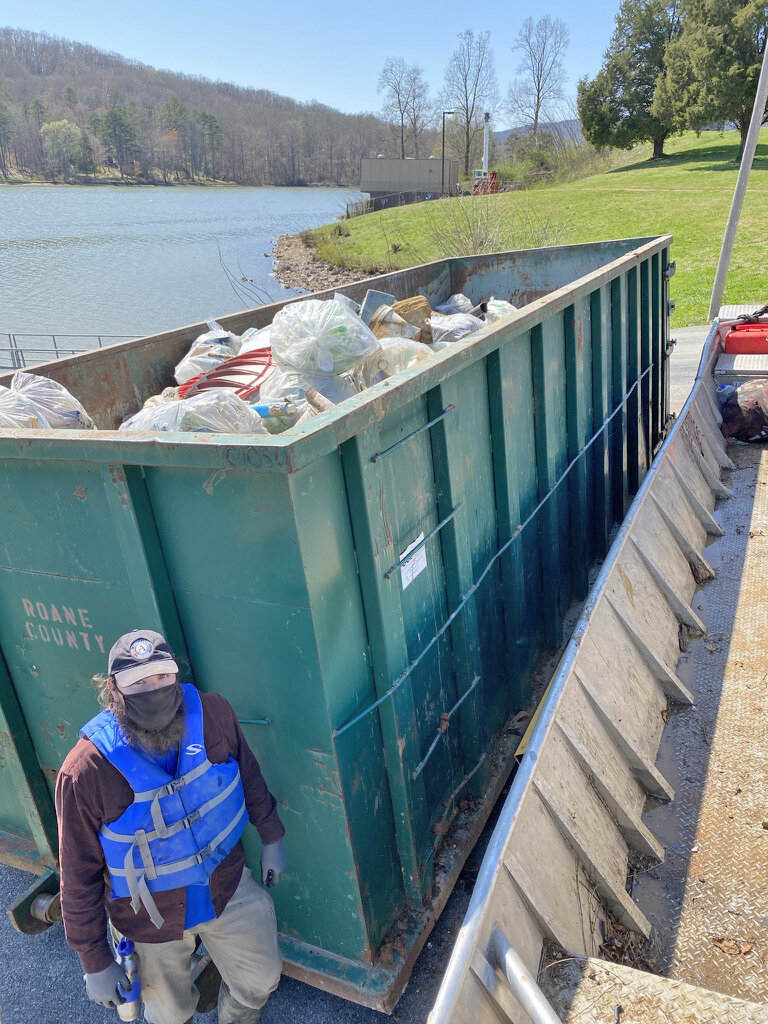 """KTNRB AmeriCorps Member, Adam Weinzapfel, stands next to the completely filled dumpster after the Roane County, Tenn. cleanup. Considering Adam is 6'3"""", you can get a visual of what 10,000 lbs. of trash looks like!"""