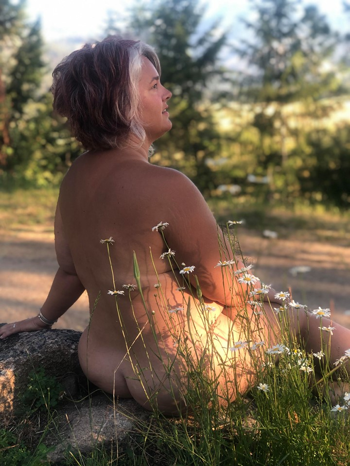 Early morning sunrise with daisies at one of our body positive group camping events; photo by Rachael Chappell