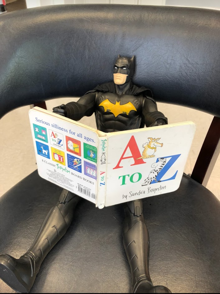 Batman takes a moment to enjoy a little light reading before his physical. *Batman is a registered trademark of DC Comics.