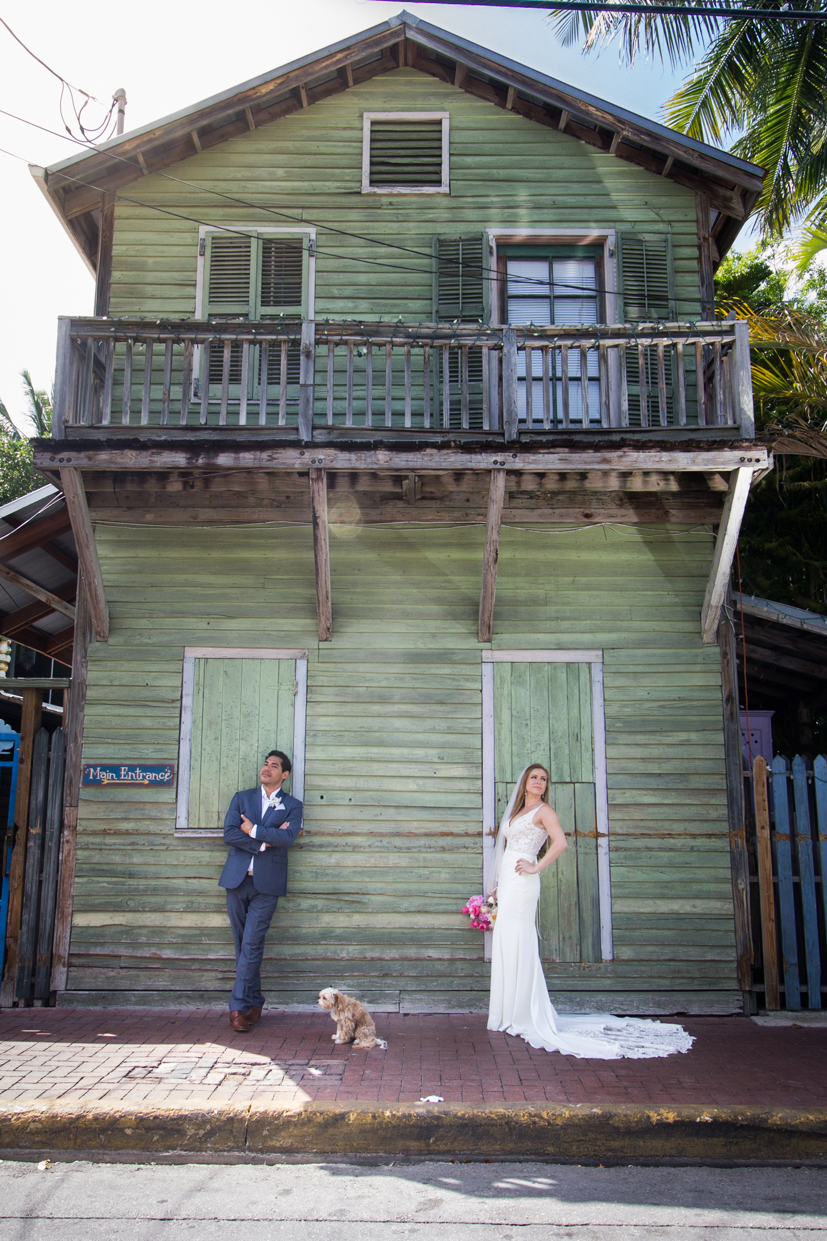 Bride-and-groom-pose-with-their-dog-in-bahama-village-key-west-on-wedding-day.jpg