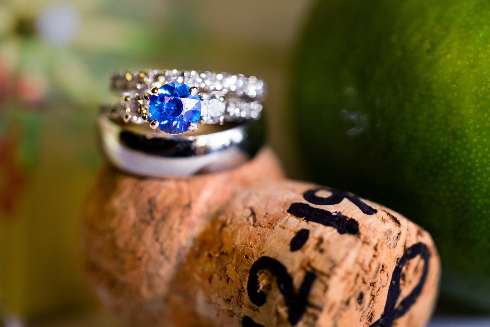 Blue-sapphire-engagement-ring-with-wedding-band-on-engraved-cork-during-key-west-wedding-details.jpg