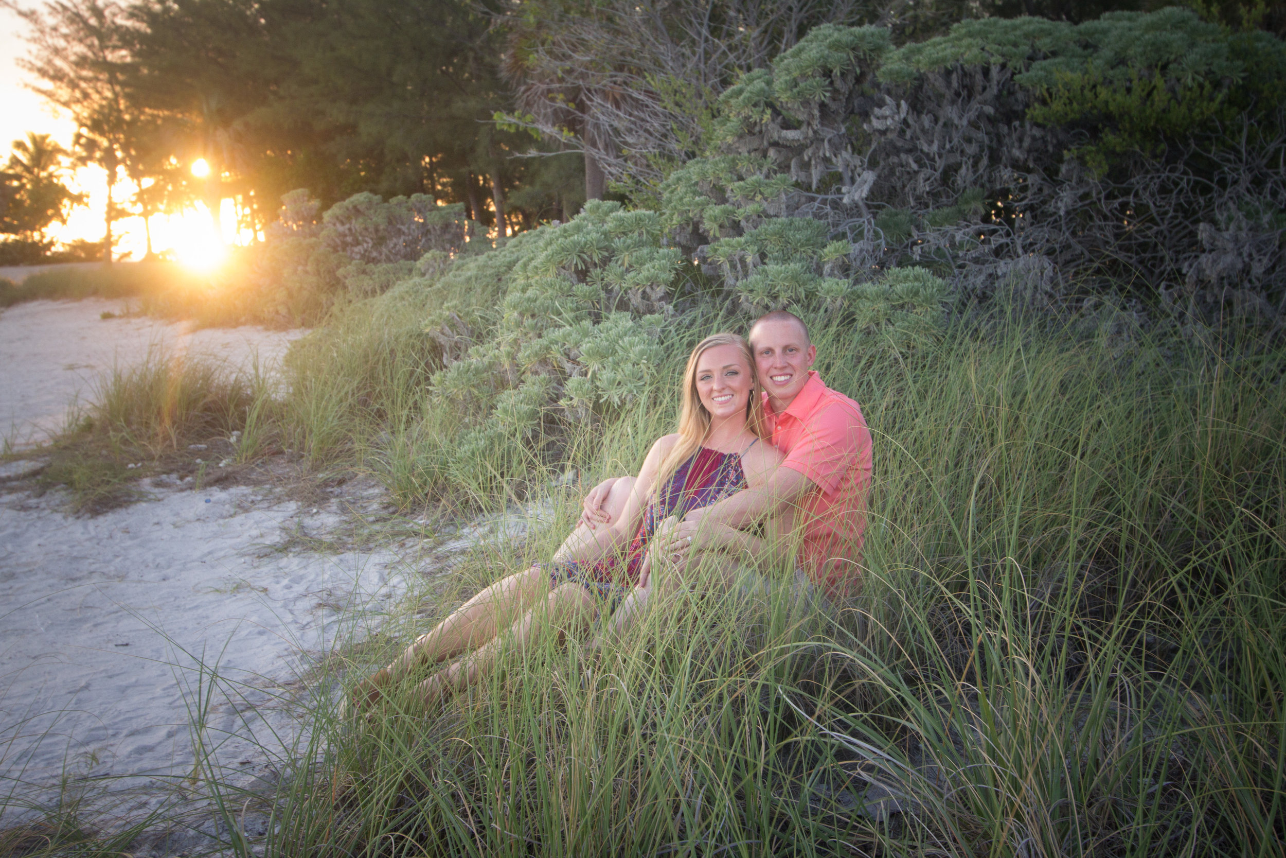 Engaged couple sit in sea grass at Fort Zachary Taylor State Park