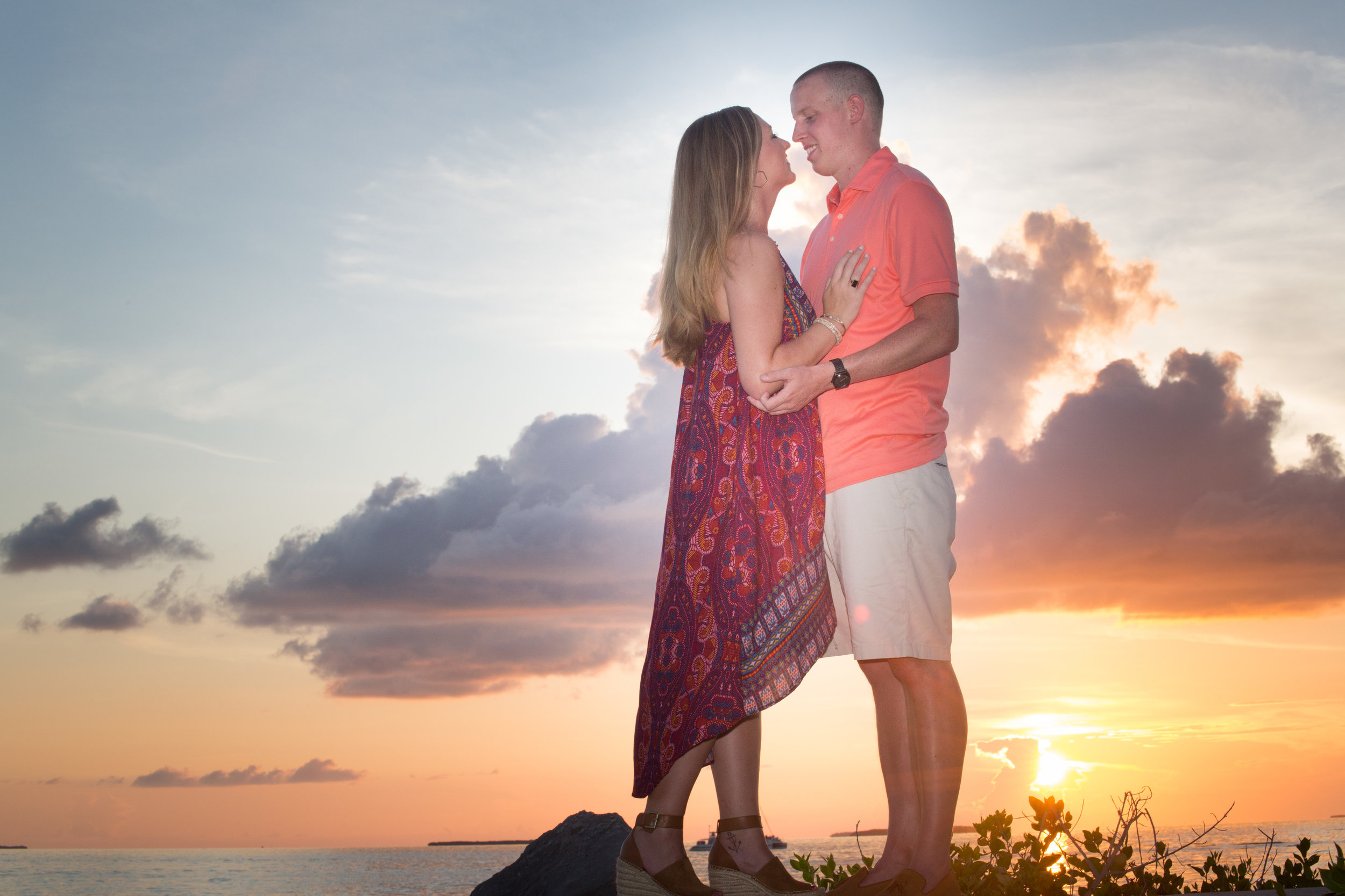 Engaged couple kiss with Key West sunset sky behind them