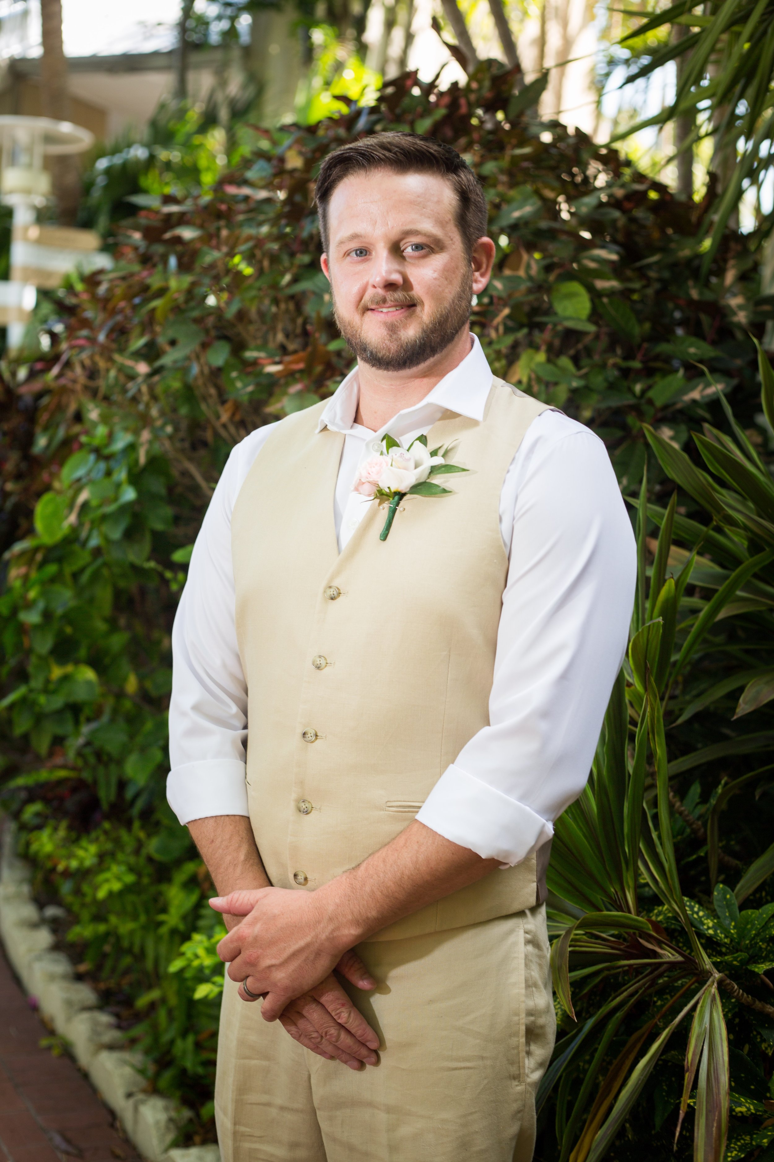 Groom stands for portrait on wedding day at Pier House Resort in Key West, Florida