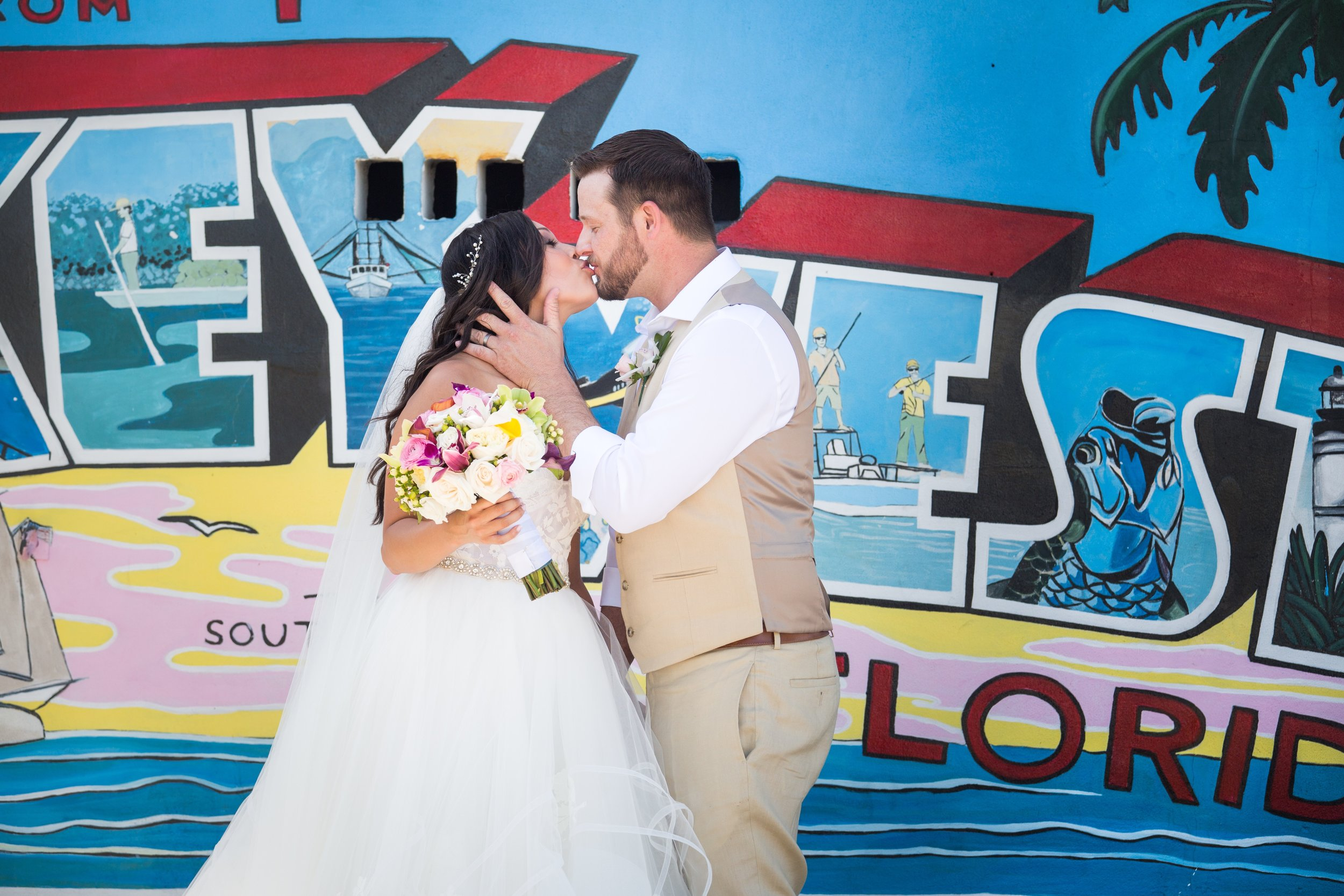 Couple kissing on wedding day in front of Key West postcard muralJPG