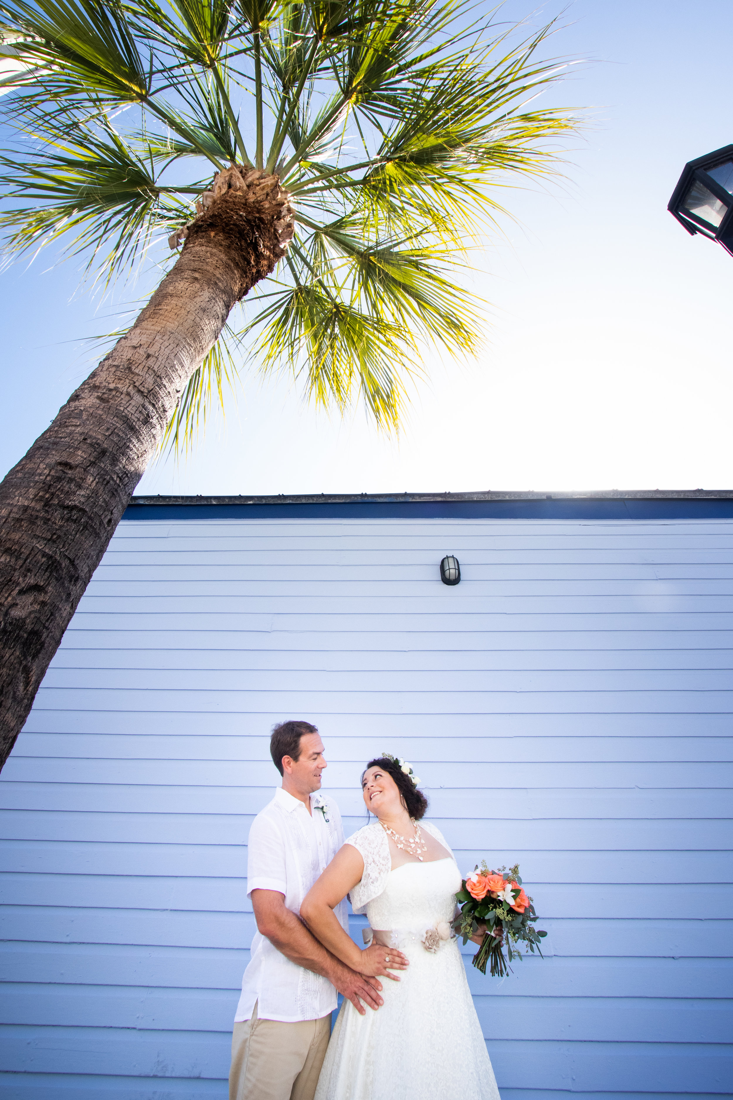 Couple during photo shoot around Key West on blue wall