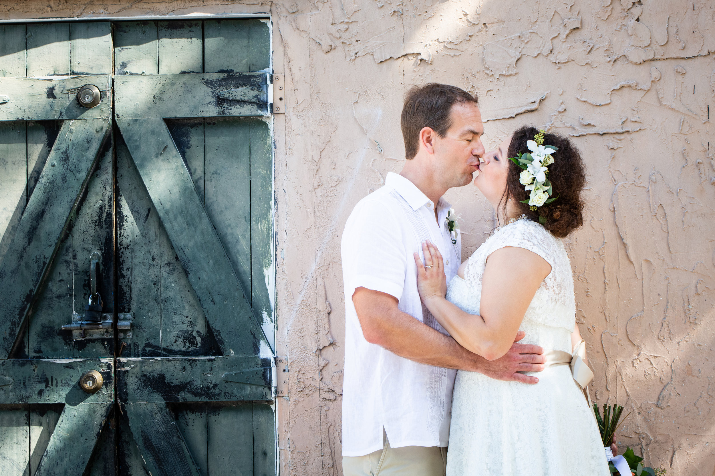 Couple Kissing Against Light Peach Wall in Key West
