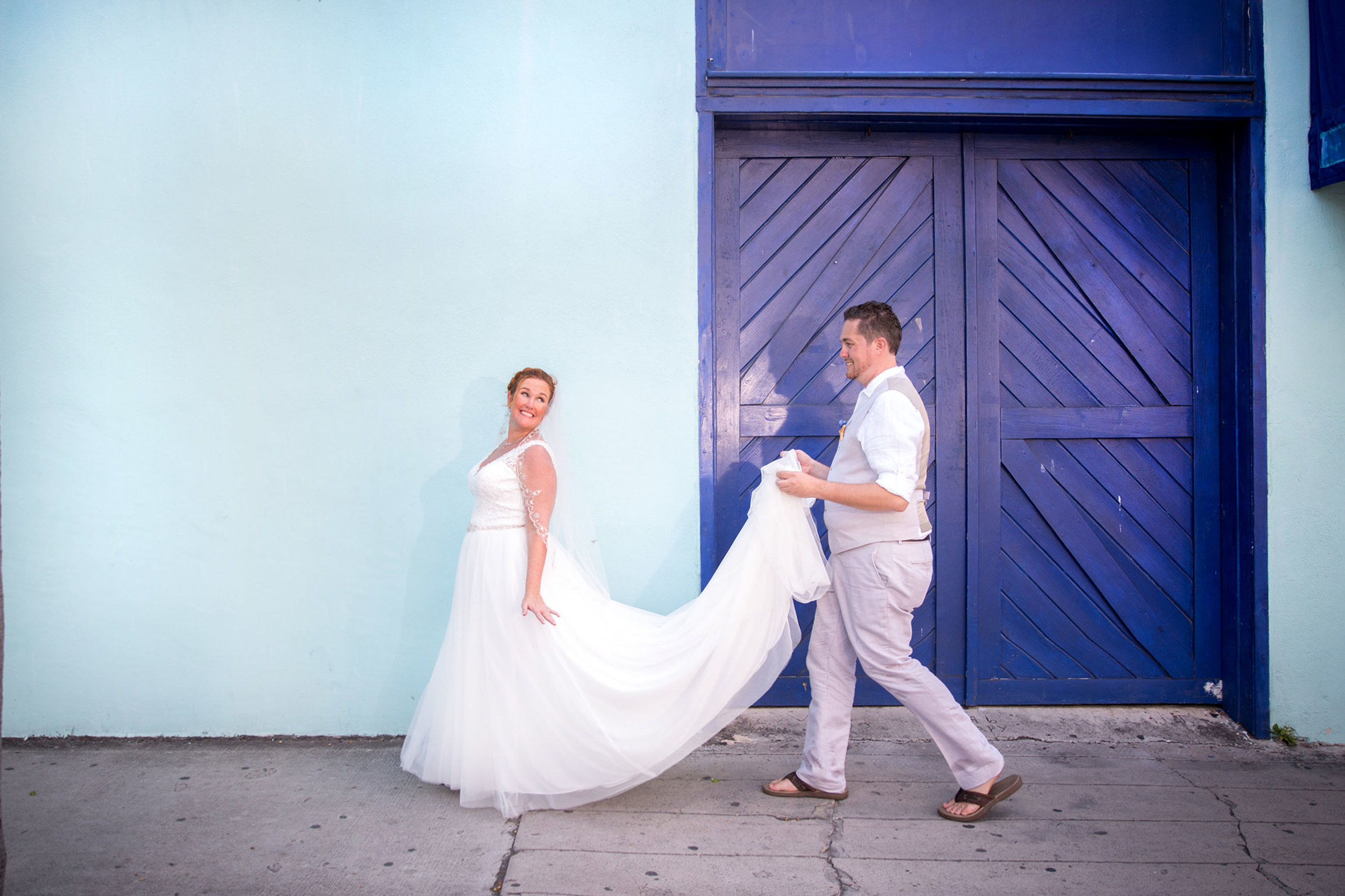 Couple Walk past light blue wall with navy door in Key West during wedding day photo shoot