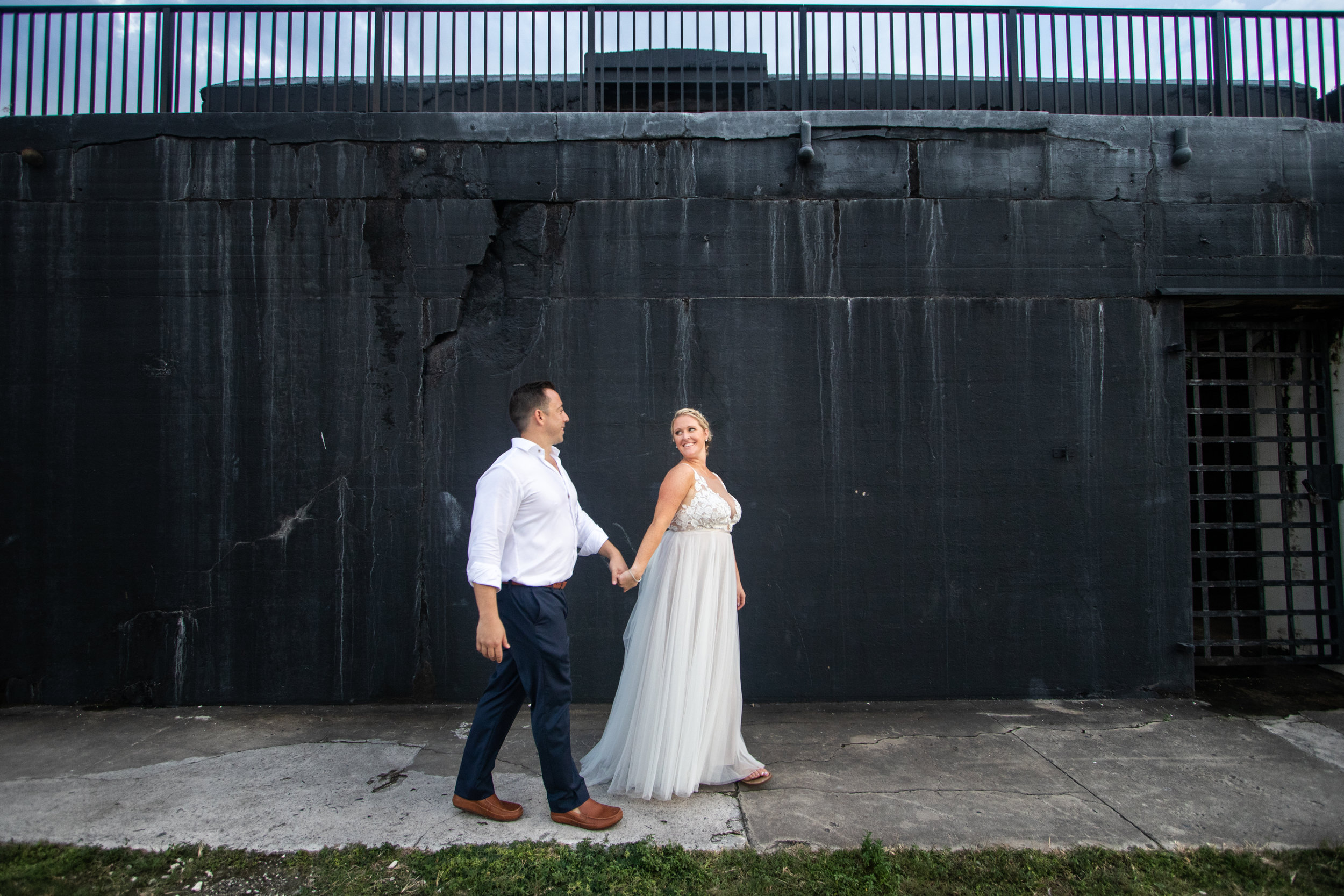 Married couple walks across black wall of Fort Zachary Taylor historic site during wedding day photos
