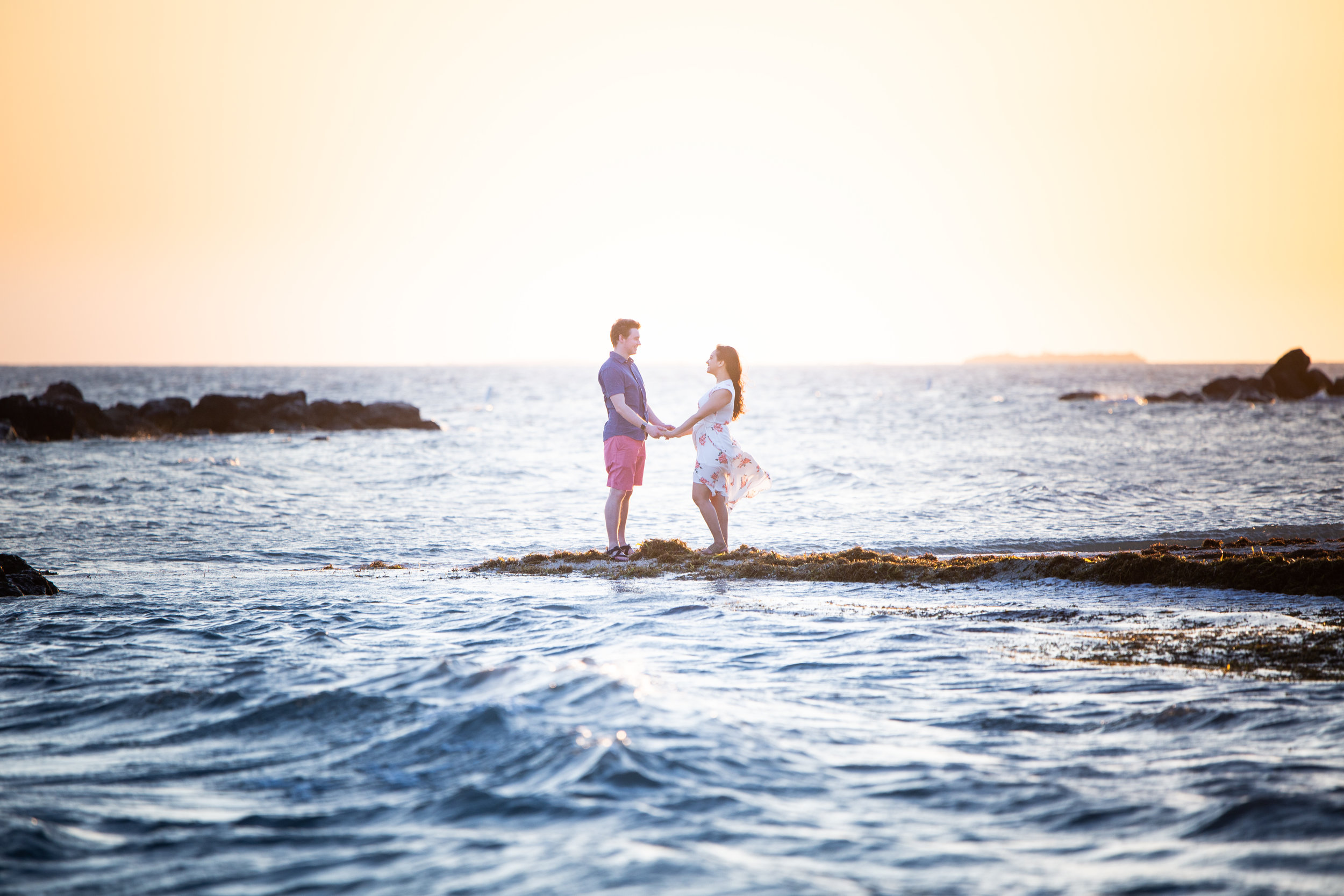Couple holding hands over water in Key West during Secret Engagement session.jpg
