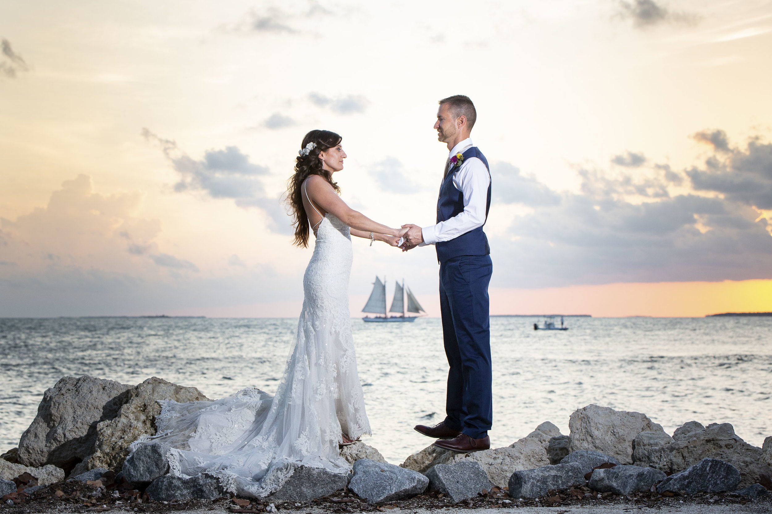 Sailboat passes behind couple during their Key West wedding