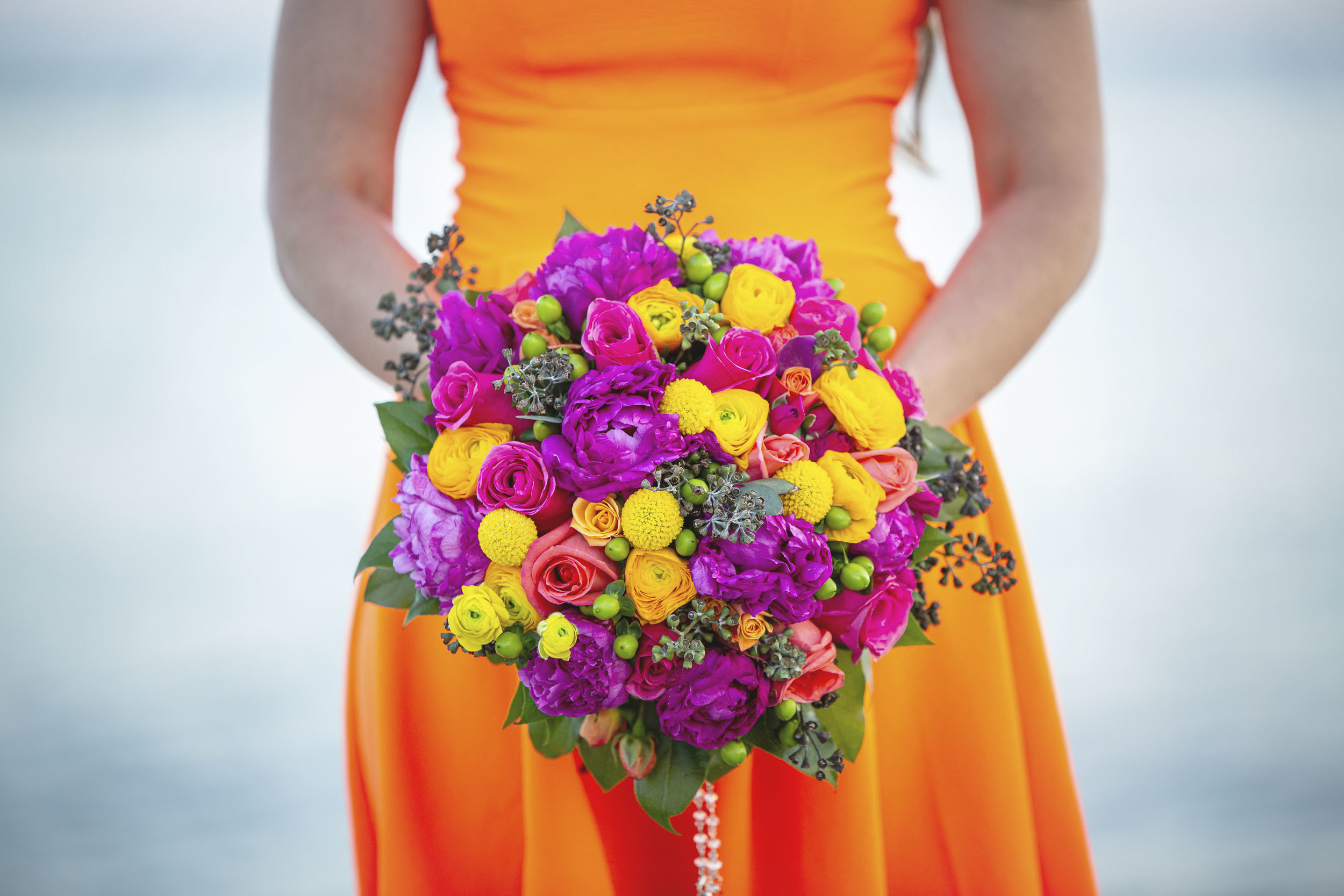 Bright bridal bouquet with orange dress for after wedding photos