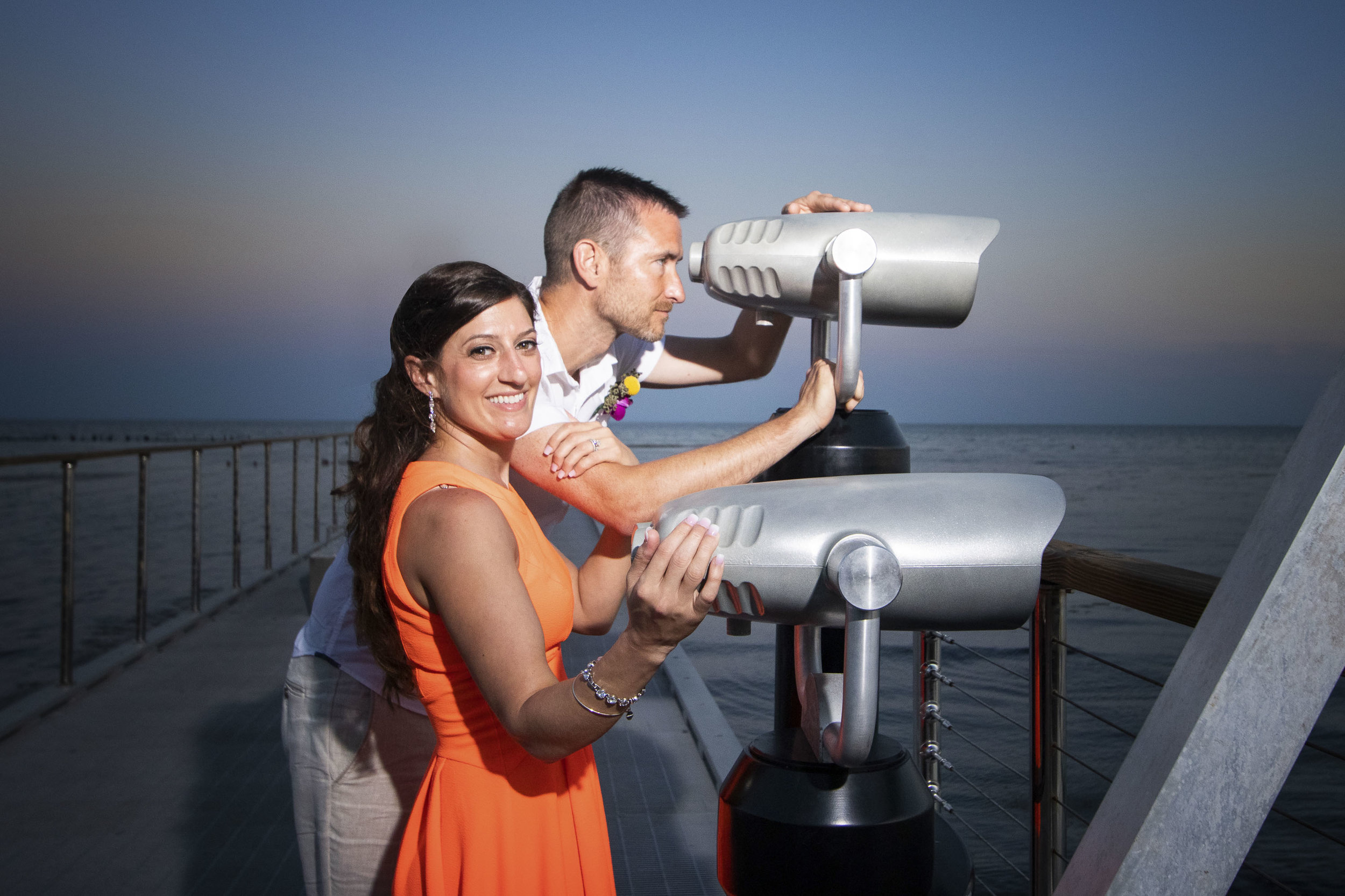 Couple looking out the telescopes on the walking pier at Higgs Beach