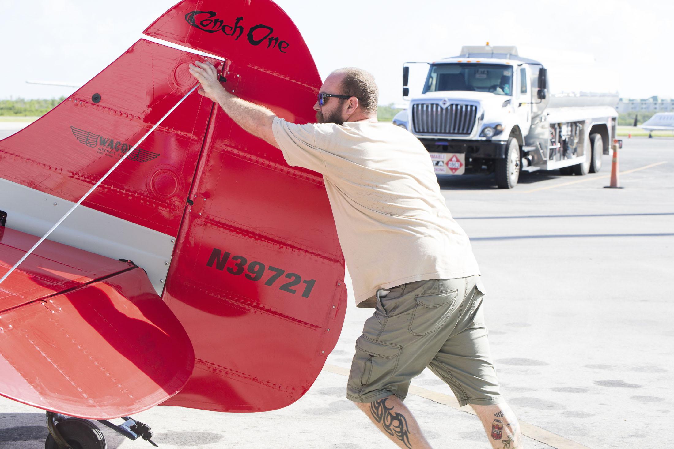 PIlot moving the plane by hand before biplane wedding.jpg