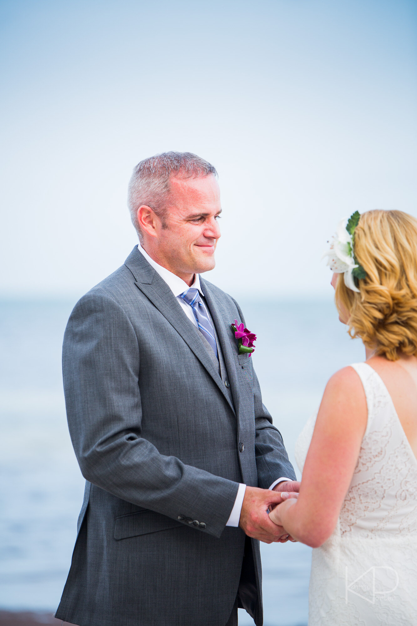 Bride peeks at camera before First Look with groom in background