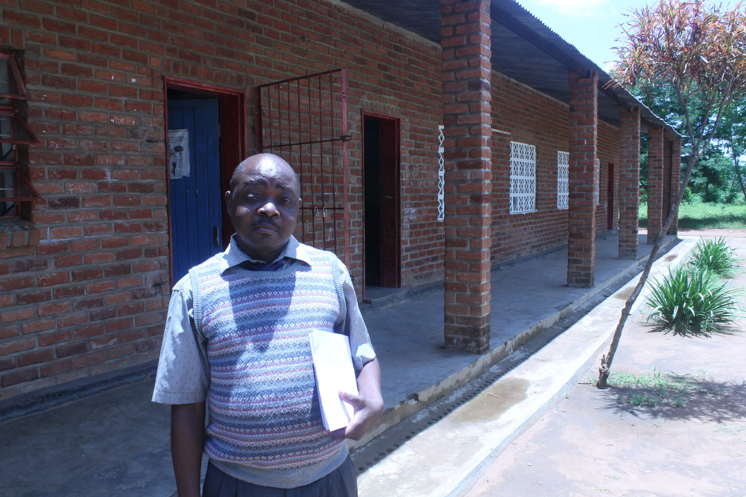 Mr. Chapata, the new Headteacher, in front of his office in the school block.
