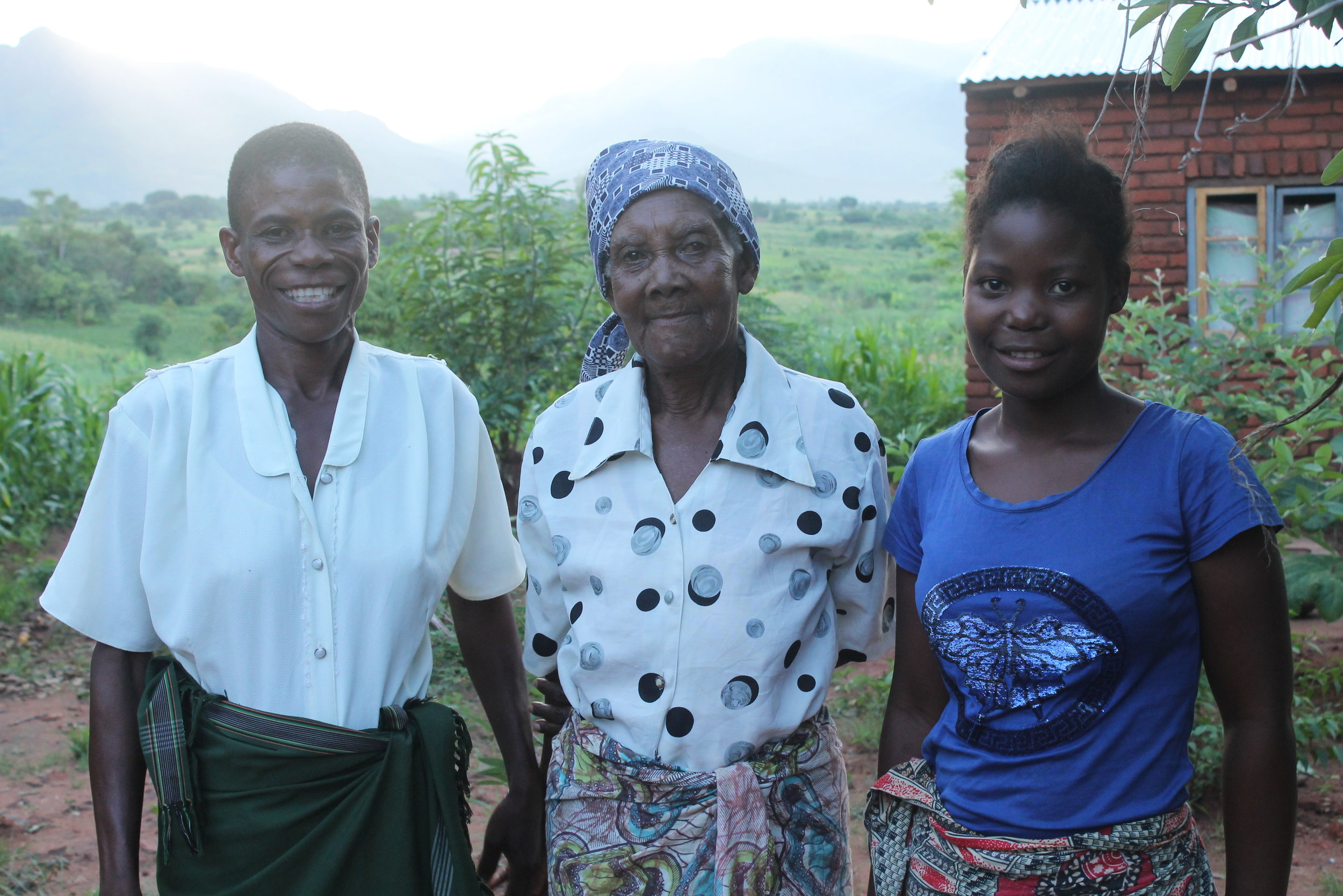 From left to right: Mother, grandmother, and Chikondi, standing on their property in January 2018.
