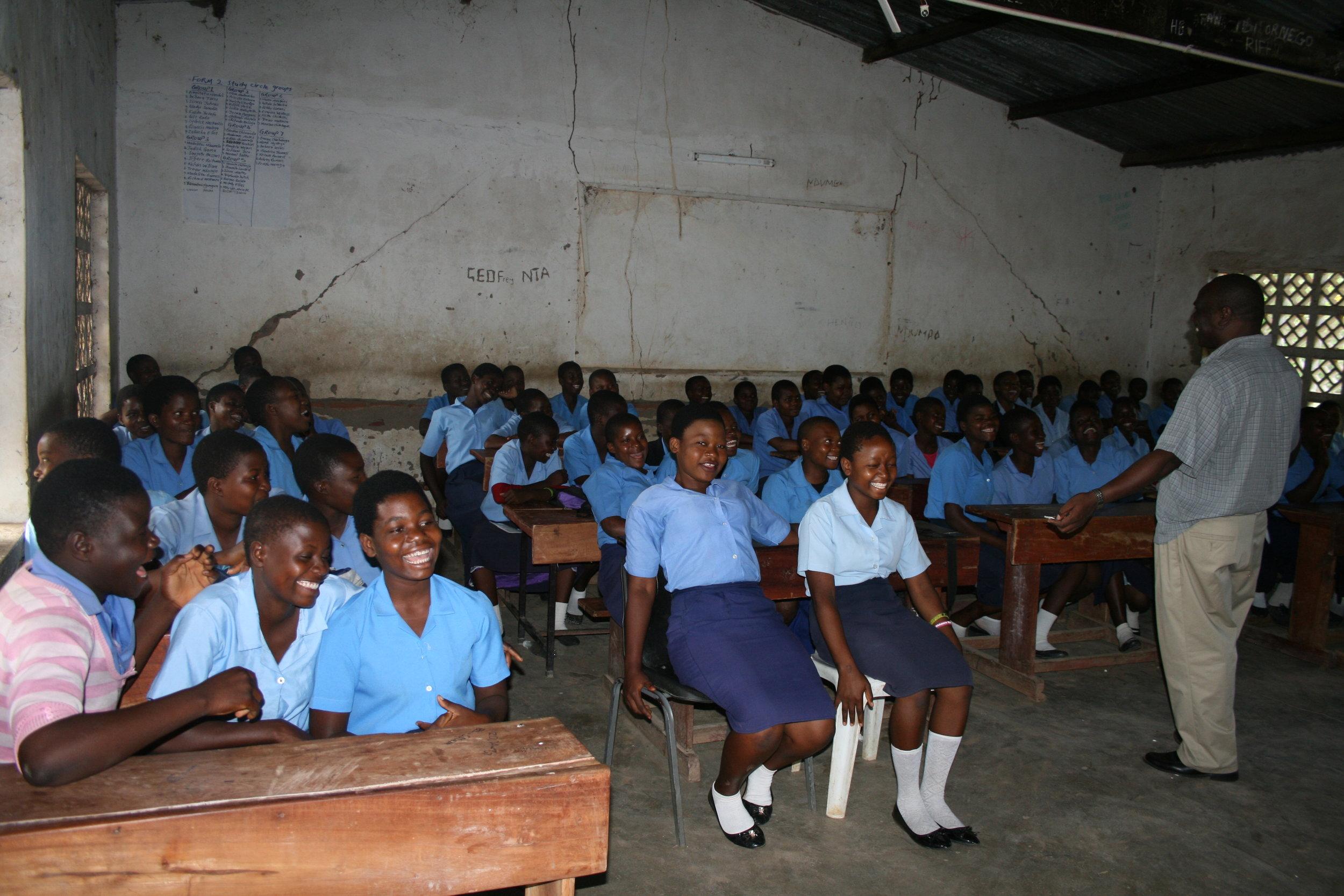 A classroom of girls giggle at Zikani's joke.
