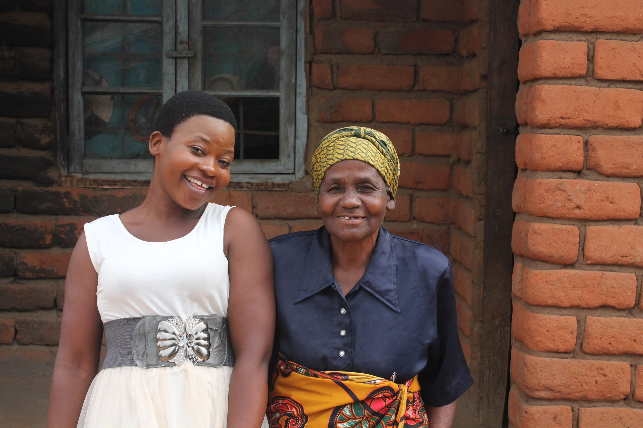 Memory and her grandmother, in front of their home.