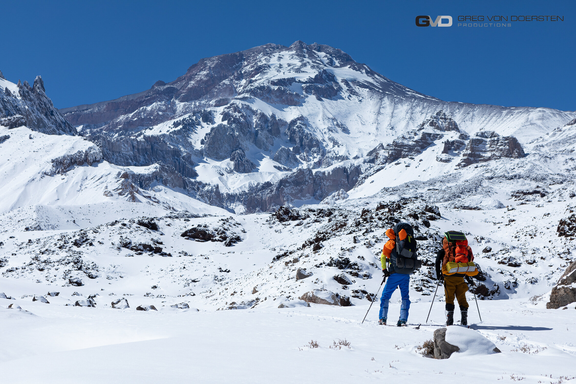 Rafael Pease & Jeremy Anderson looking at Volcan Tupungato with 1 of their 2 backpacks.