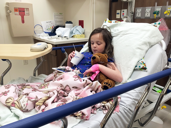 Post-procedure. Abbey jumped right into her element. Slushy, iPad and Teddy Bear.