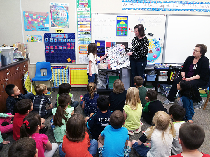"""Abbey and Shauna sharing Abbey's """"All About Me"""" birthday poster to her class."""