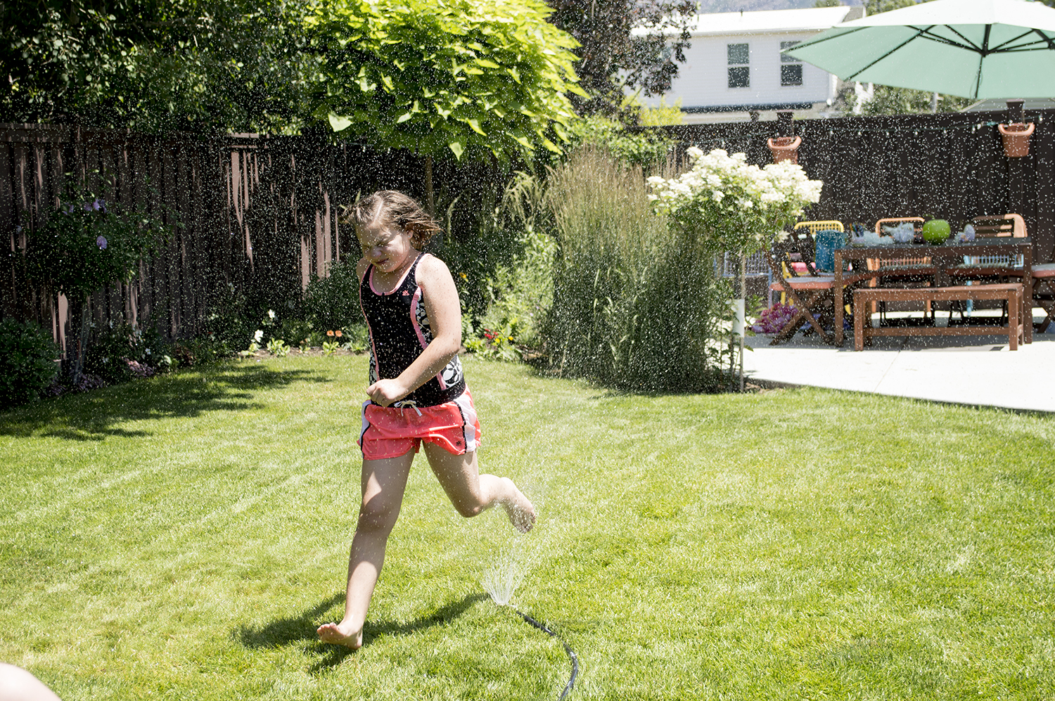 Marisa running in the sprinkler.