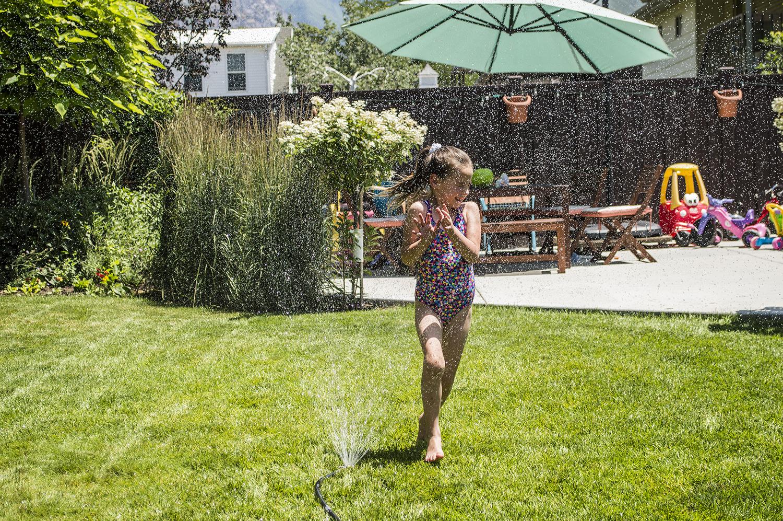 Maliya running in the sprinkler.