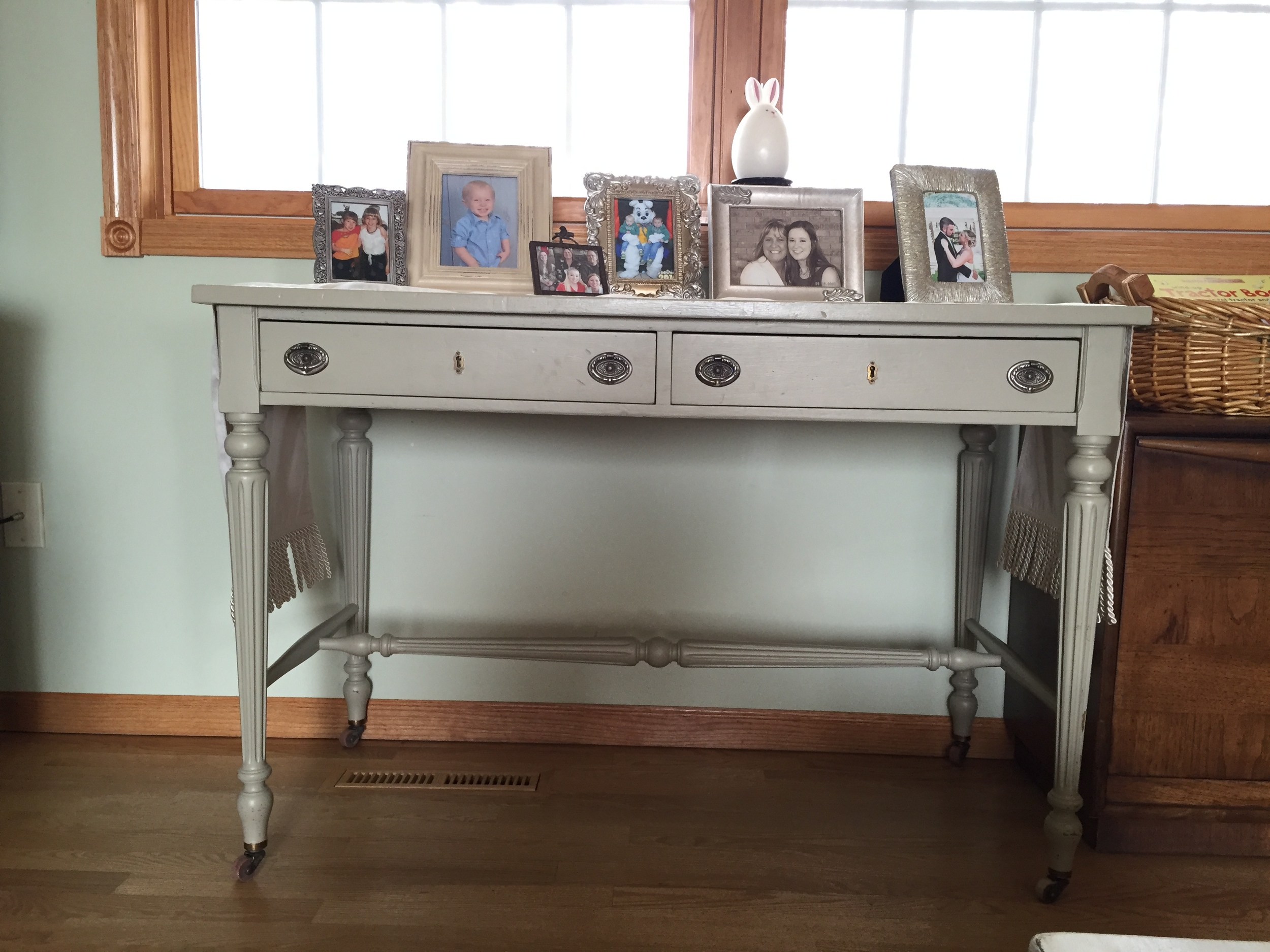 An antique library table in Julie's home displays family photos.