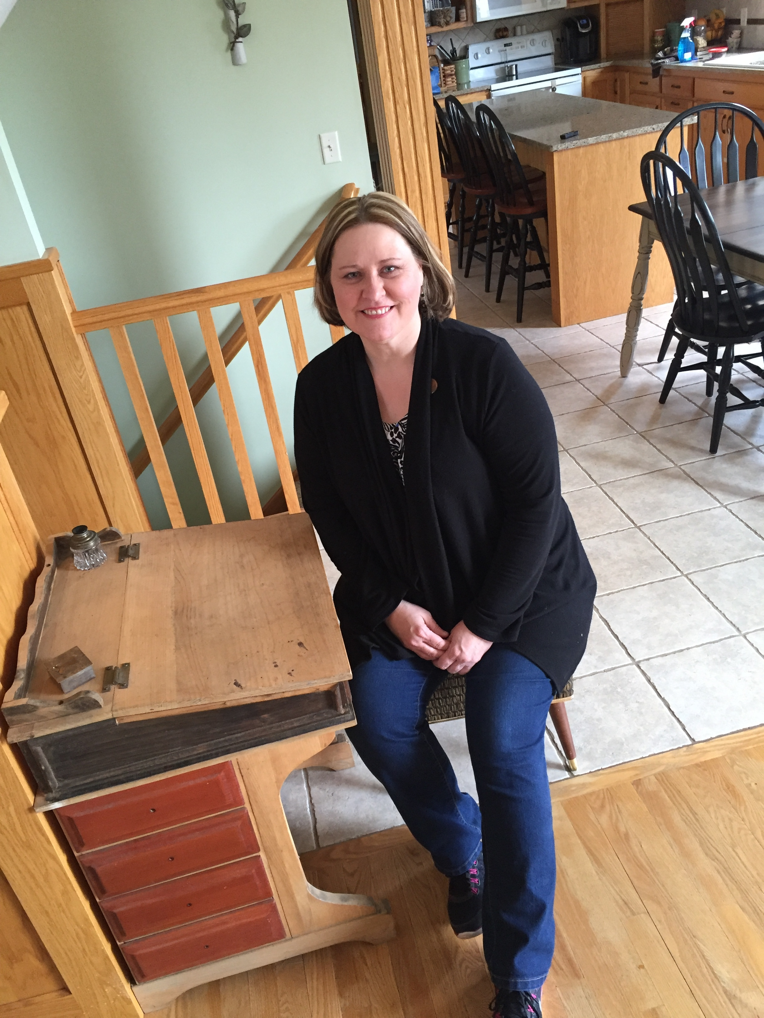 "Julie sitting at an antique school teacher desk she found at a garage sale for $7. ""I enjoy the process and letting something speak to me. Like this desk...it hasn't spoken to me yet what color I should paint it."""