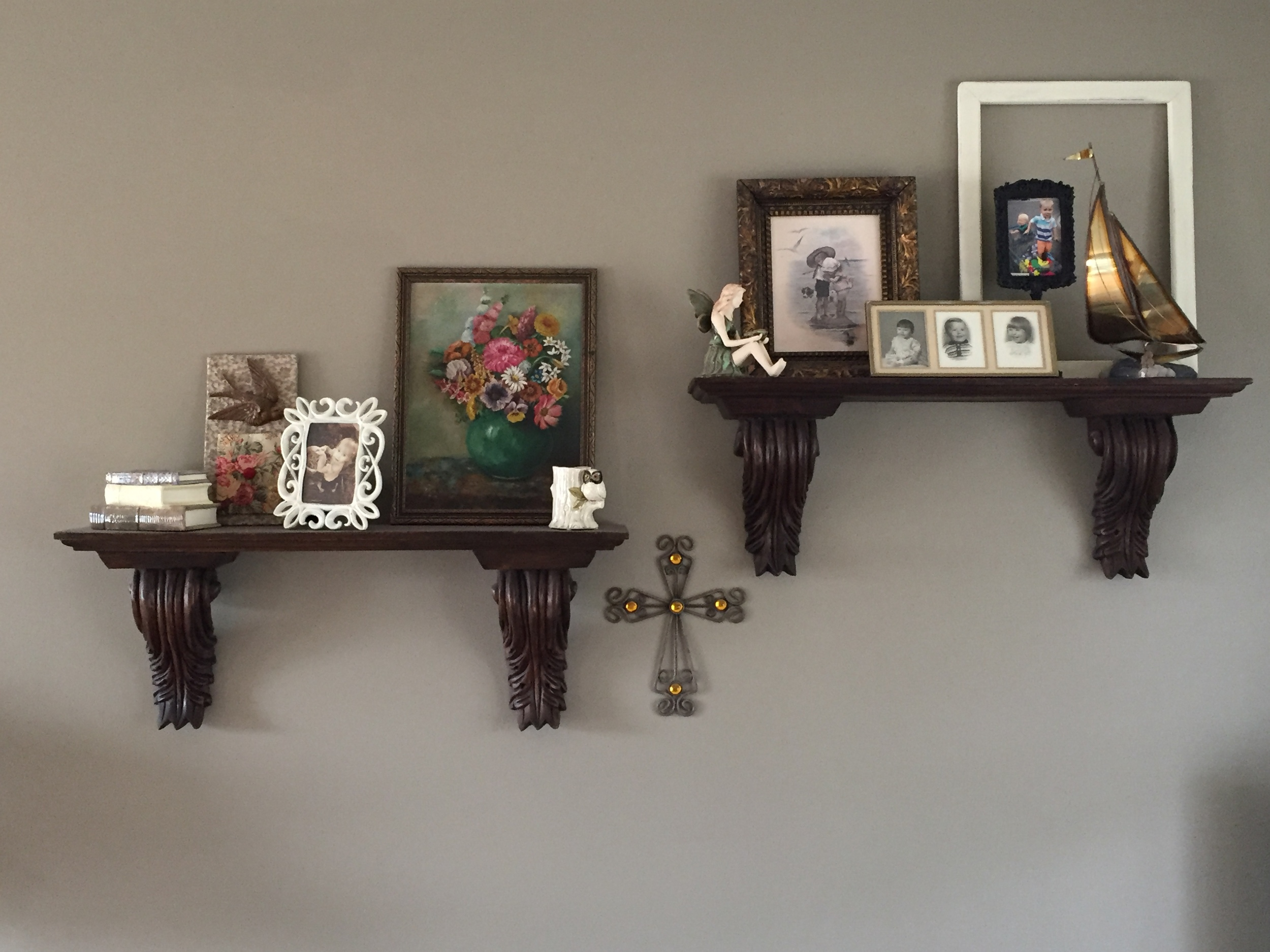 """I like that spot,"" Julie says about her wall shelving which displays old pictures of family, a vintage floral painting, and her love of birds."