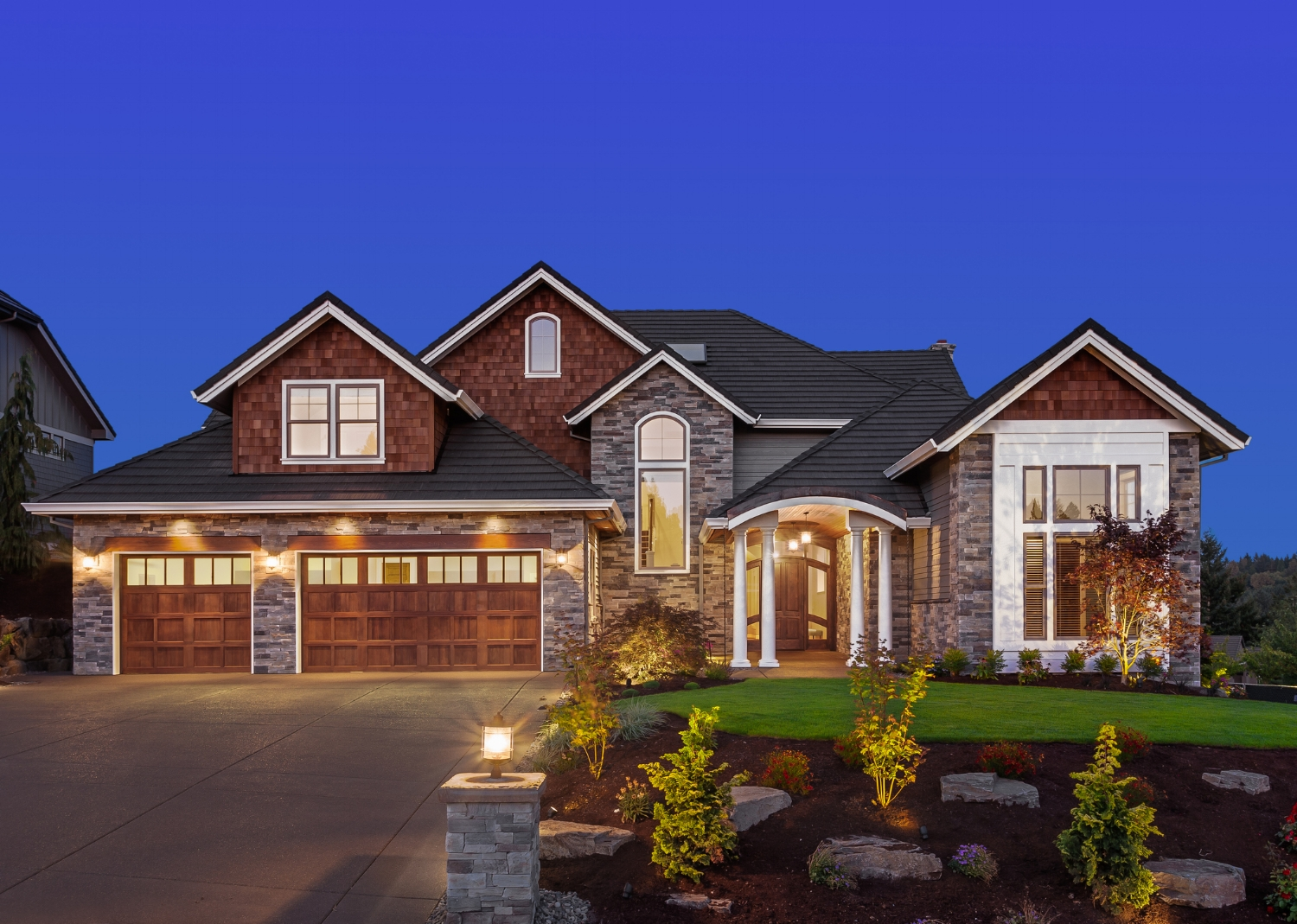twilight photo of a beautiful home with a great landscaped yard.