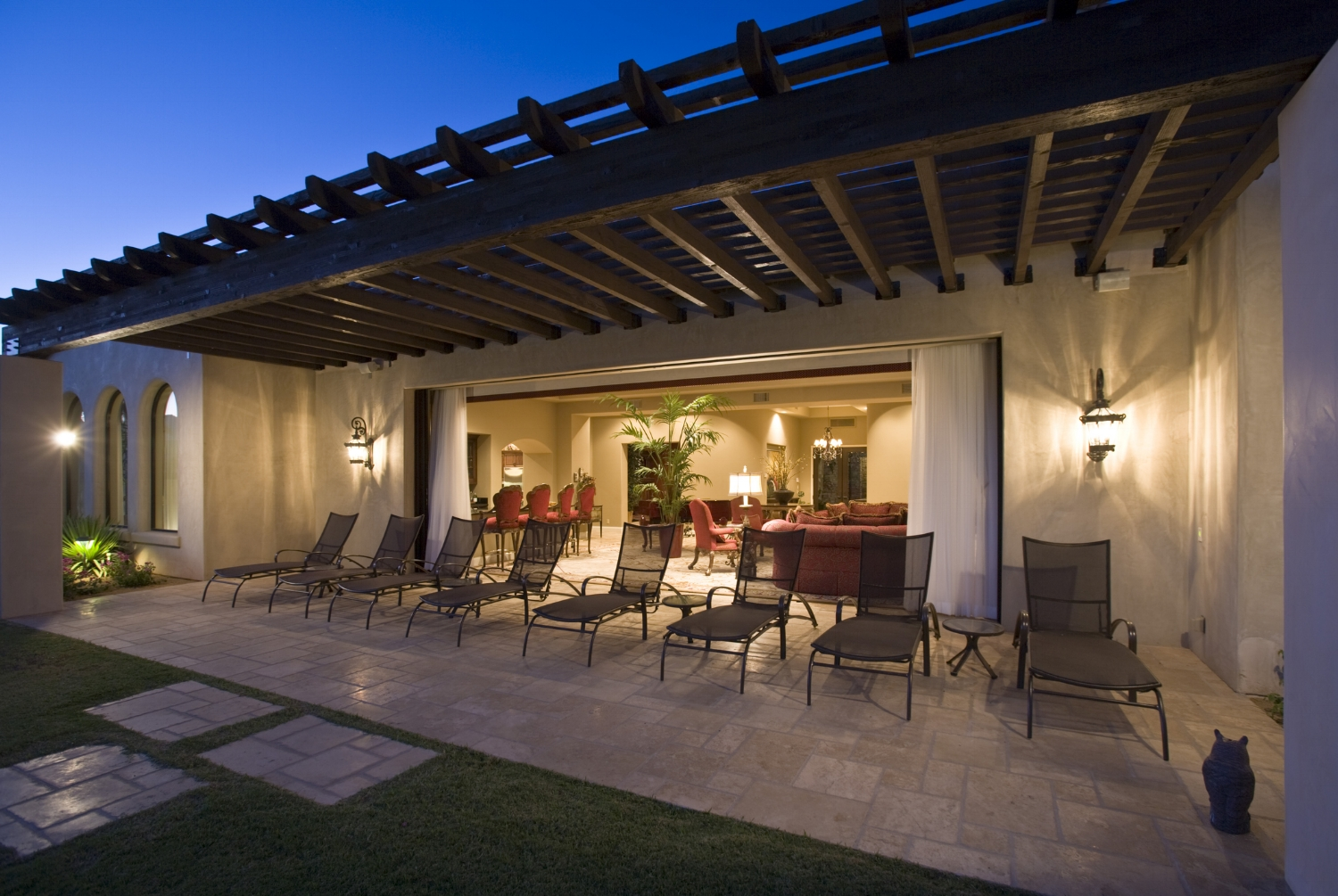 a back patio lit up at night with an open california feel.