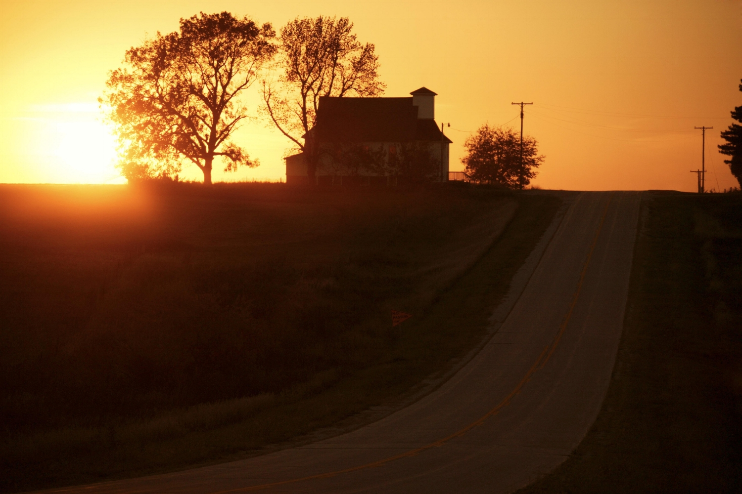 a sunrise marketing photo of a farmhouse basking in the morning glow of the sun on it's 30+ acres of land.