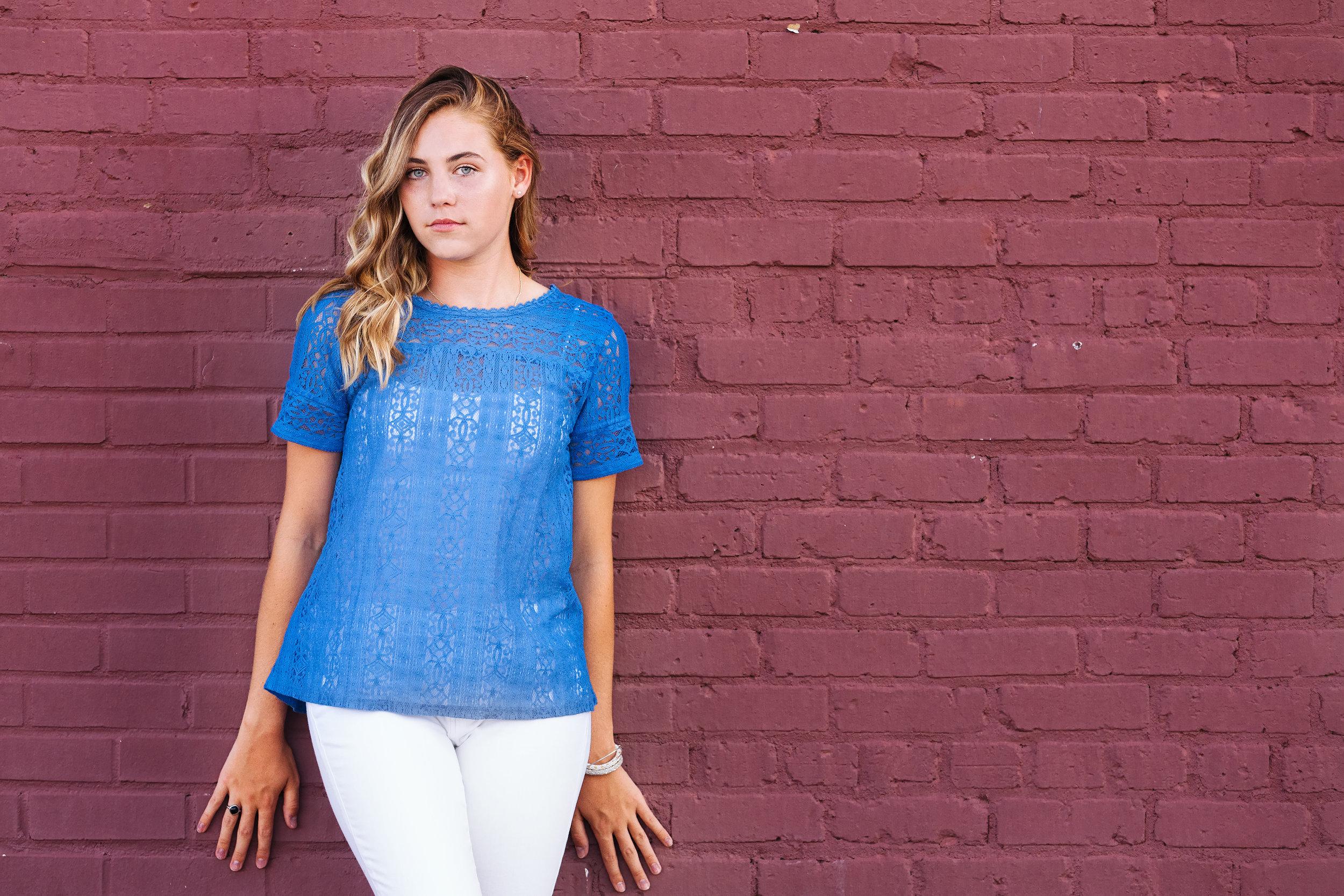 looking-at-camera-blue-shirt-maroon-wall.jpg