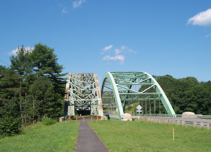 The 1937 Justice Harlan Fiske Stone Bridge in Chesterfield was bypassed by the larger bridge (right) in 2003. A nonprofit group formed to beautify and maintain the pedestrianized bridge, but it dissolved in 2016.