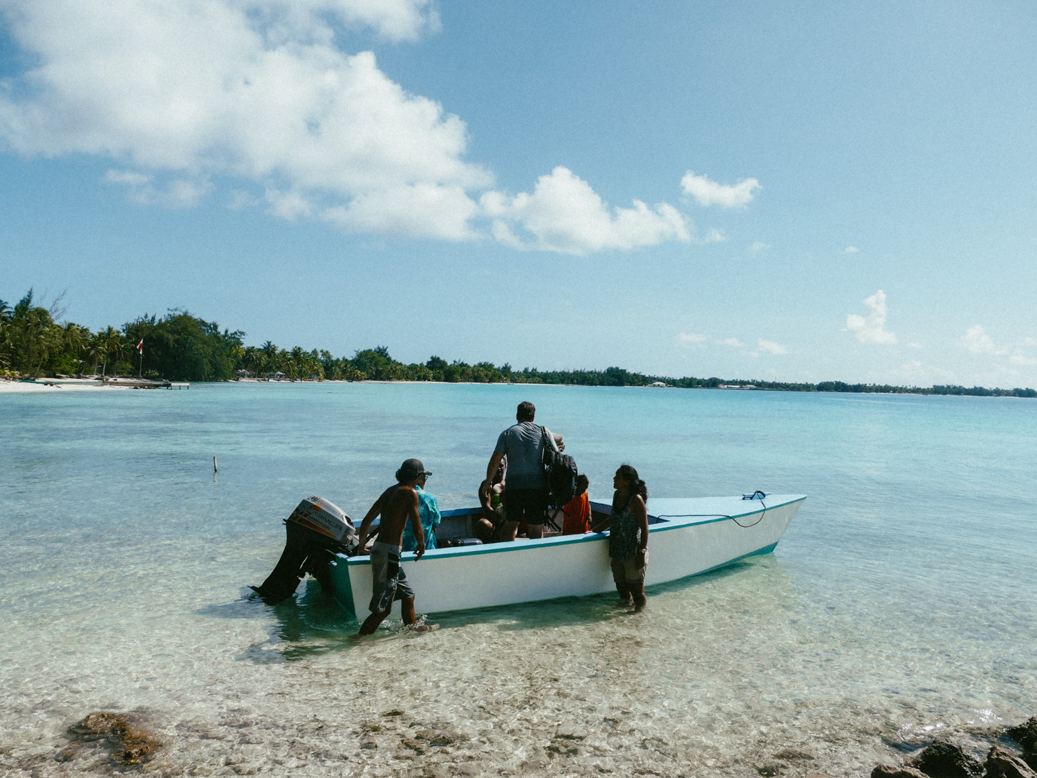 People getting in a boat on Tikehau, Tuamotus, French Polynesia, South Pacific.