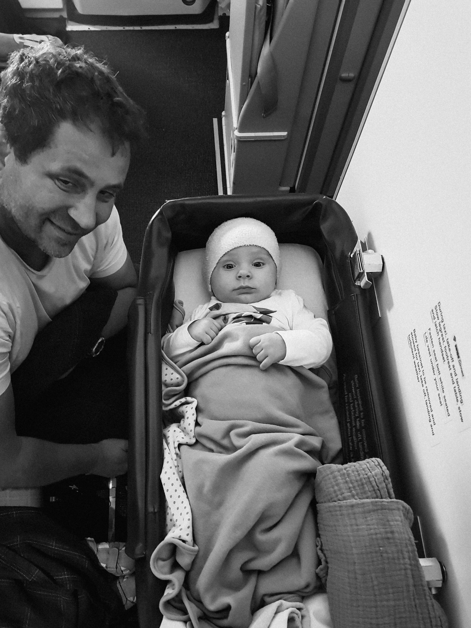 A baby looks up from an airplane bassinet.