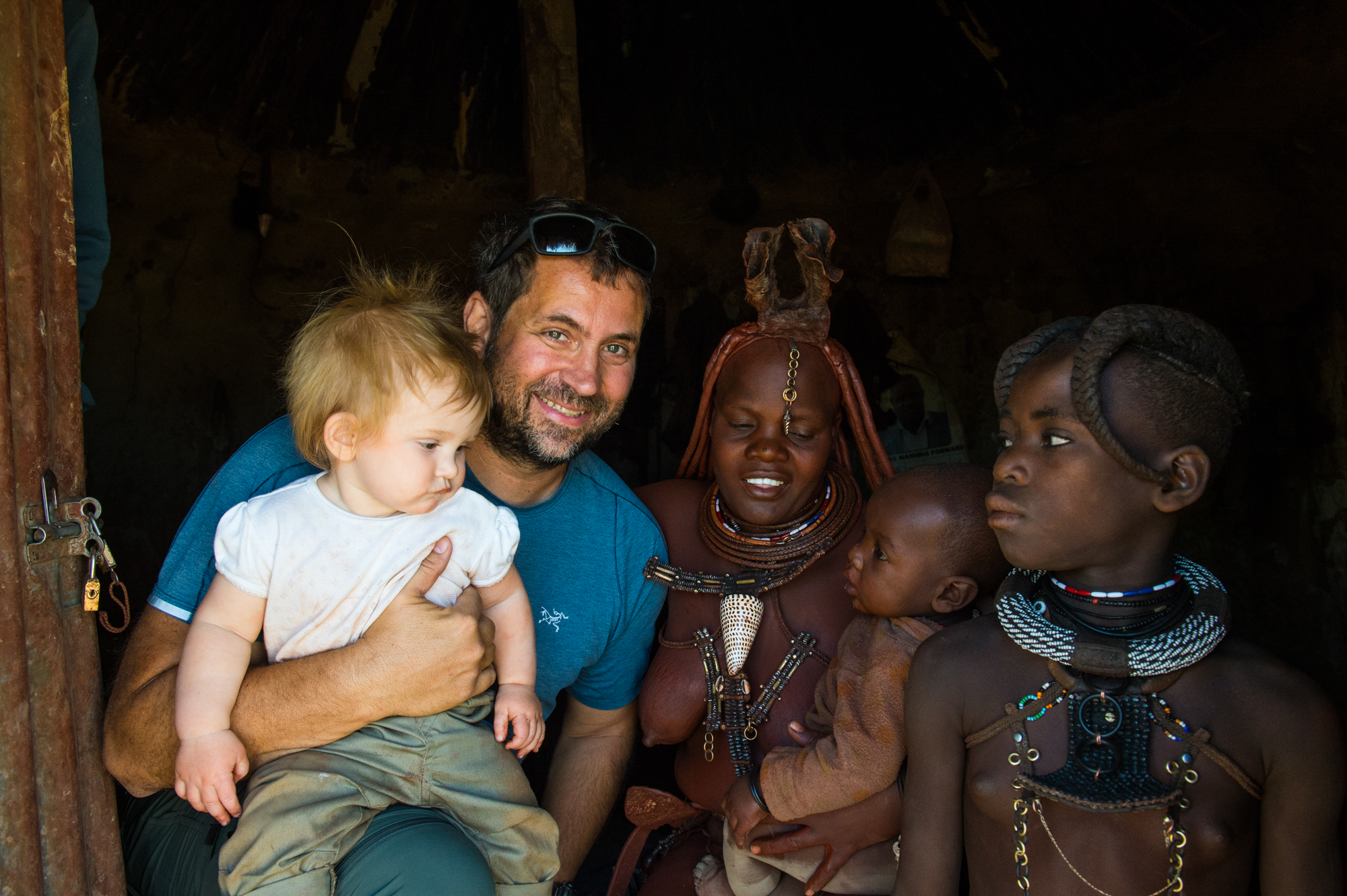 White tourist with his baby in a Himba village, Kaokoland, Namibia