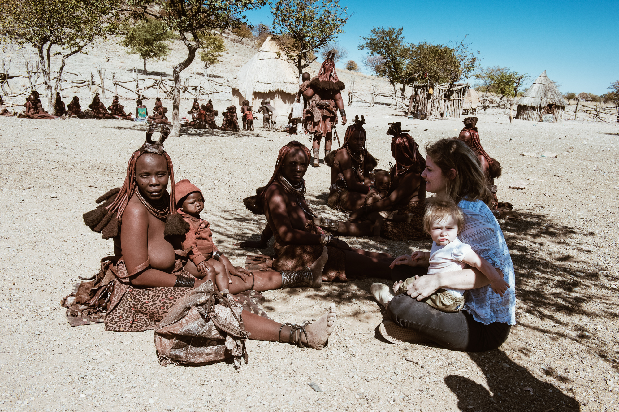 White tourist with a baby interacting with Himba women, Kaokoland, Namibia