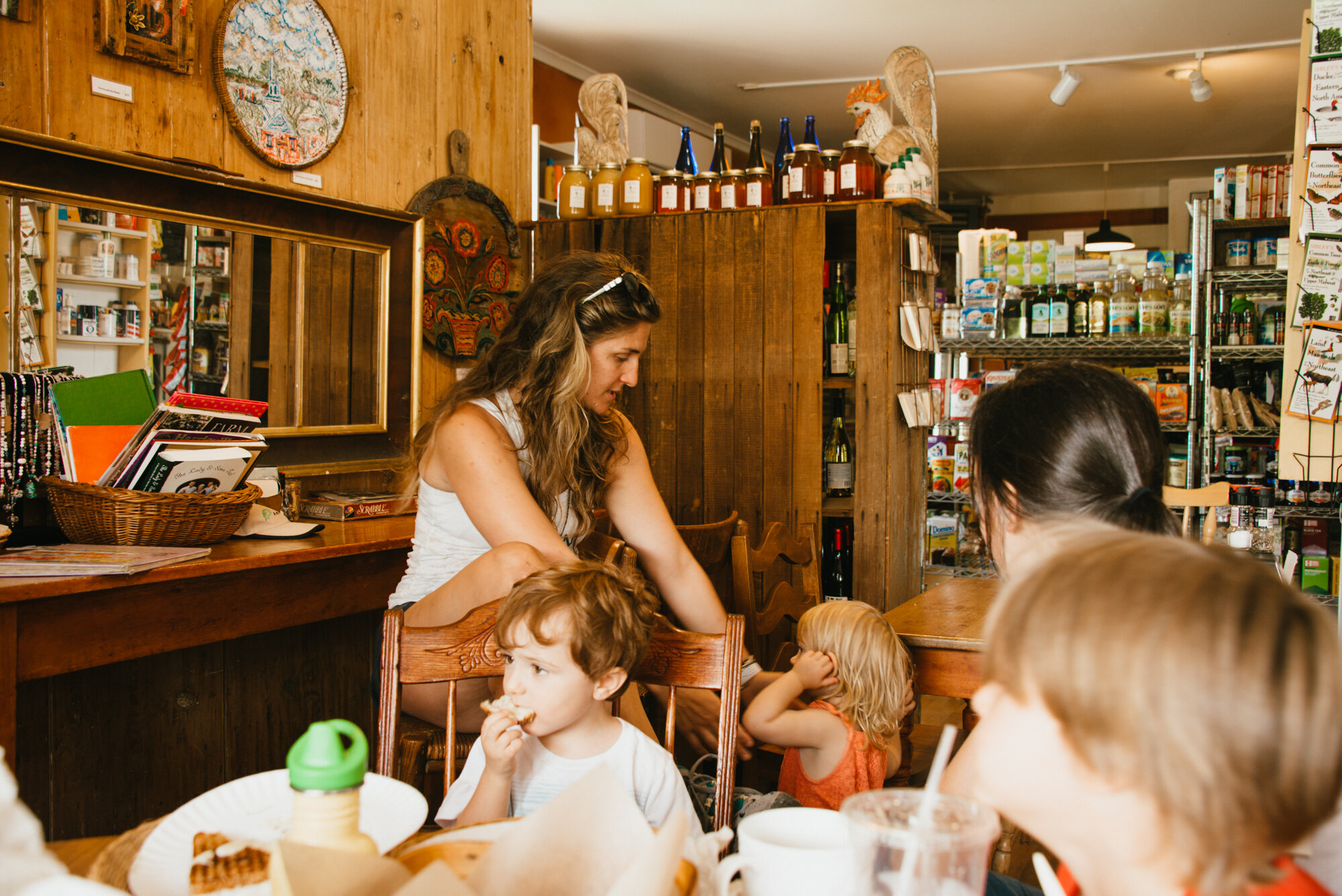 A woman surrounded by kids in a general store in Harrisburg, New Hampshire, United States.