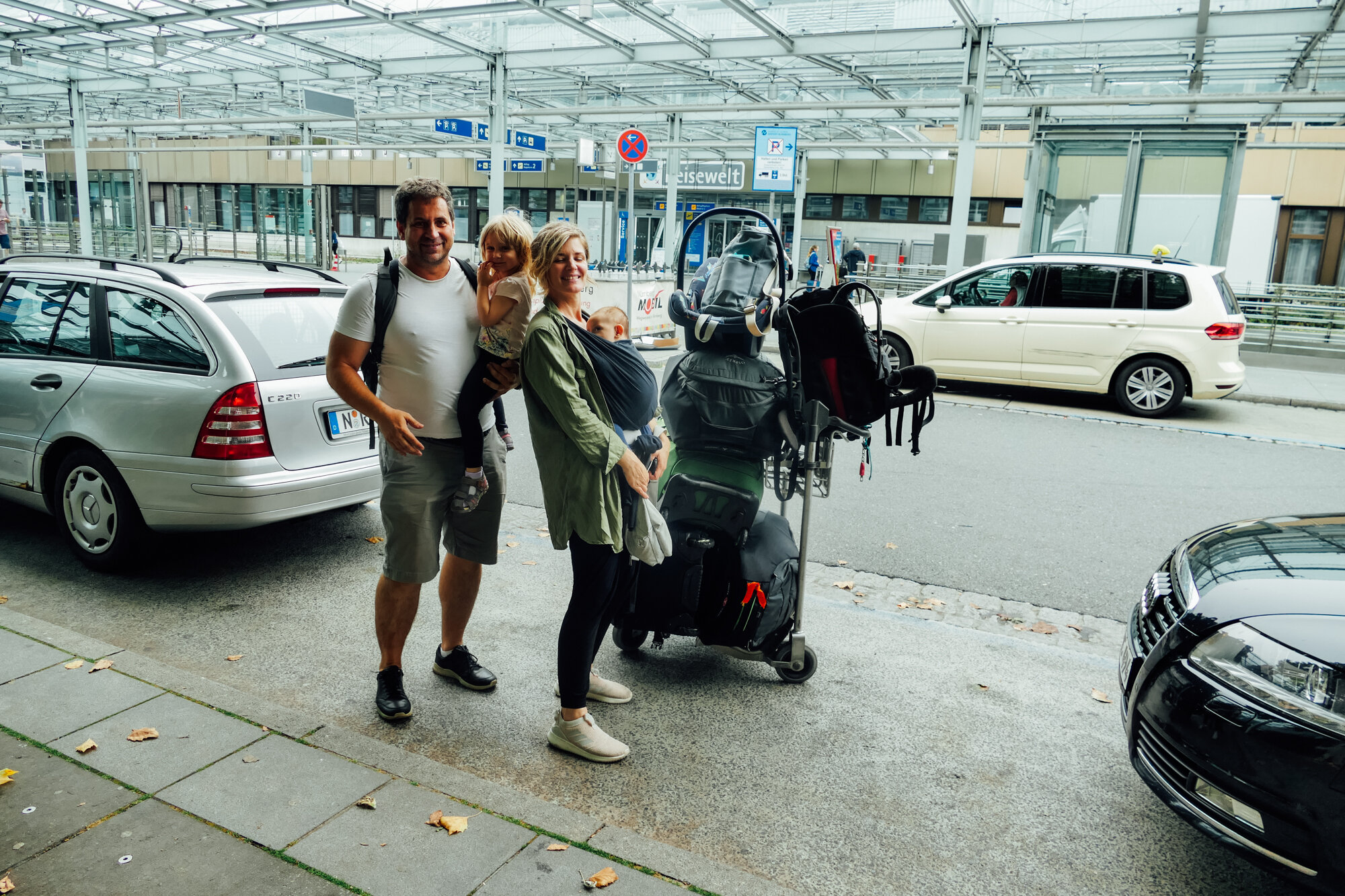 Family stands on curb at airport with baggage
