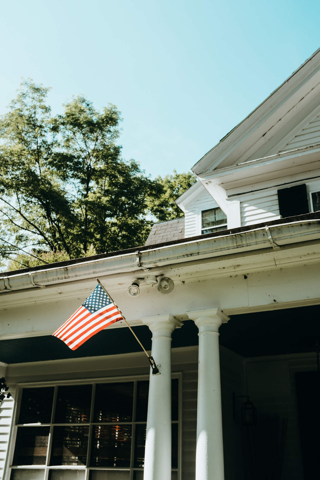 An American flag blows in the wind on the front of the Monadnock Inn, New Hampshire