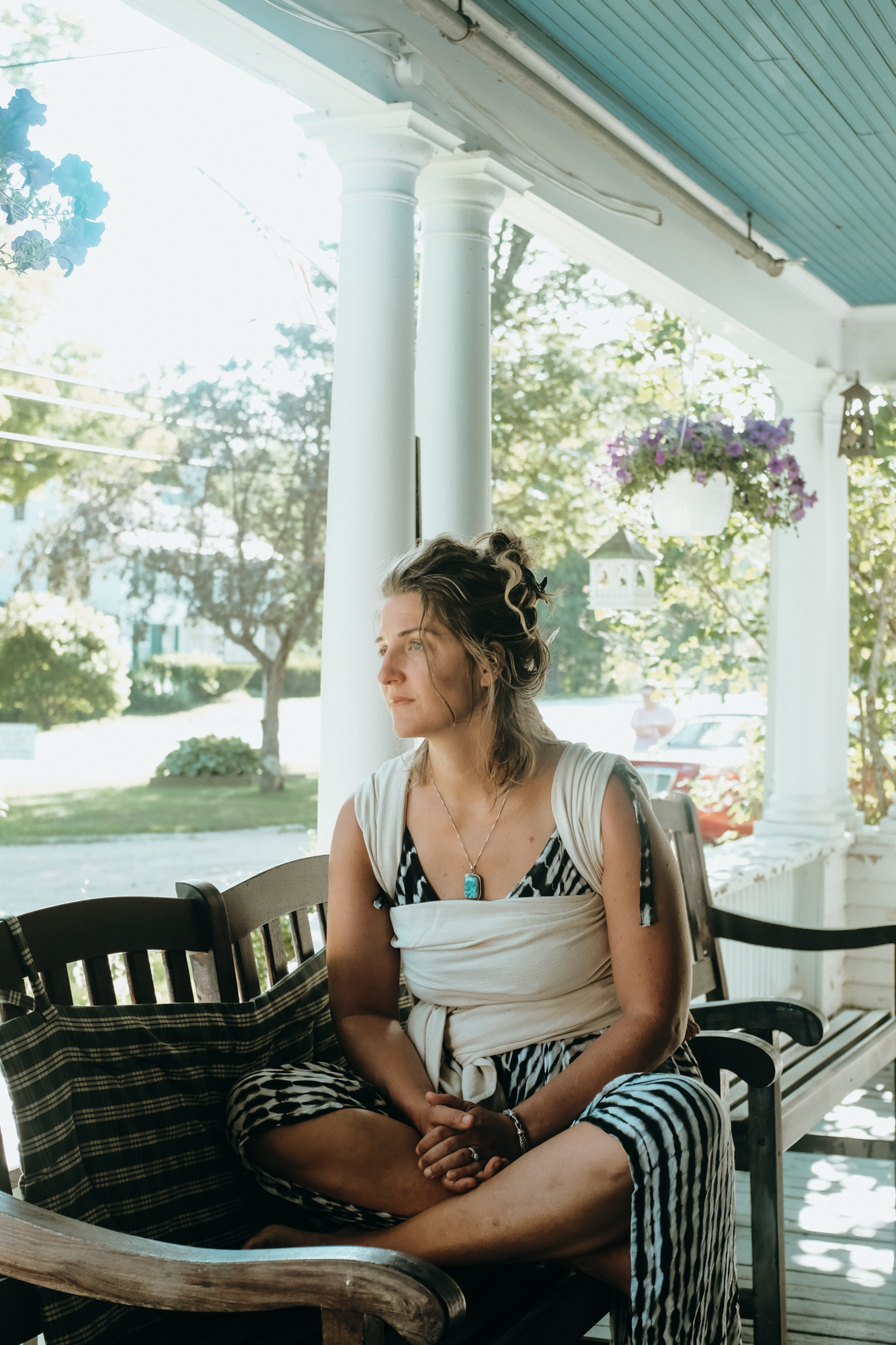 A mother carries a baby in a baby wrap carrier on her back on a porch in New Hampshire, New England.